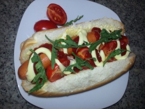 Dog with tomatoes, rocket, tomato and mayo drizzle